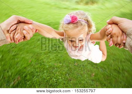 Close up portrait of little girl being spun in circles at park by her father