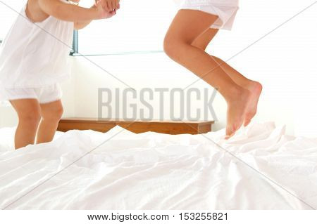 Low section portrait of two little girls jumping on bed