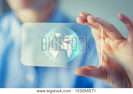 business, technology, international communication, mass media and people concept - close up of woman hand holding and showing transparent smartphone with globe on screen