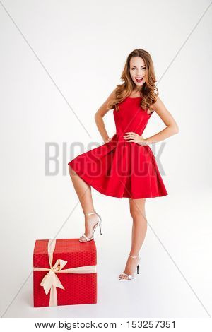 Full length portrait of a cheerful brunette woman in red dress standing with one leg on a big gift box isolated on a white background