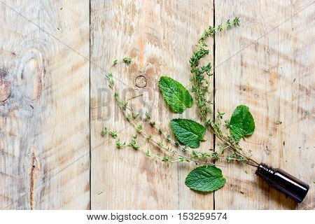 fresh summer herbs - aromatherapy at wooden background top view