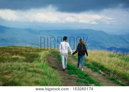 Couple of handsome bearded man in white shirt and pretty young cute girl or woman in black hoody holding hands and walking on meadow road on blue sky background