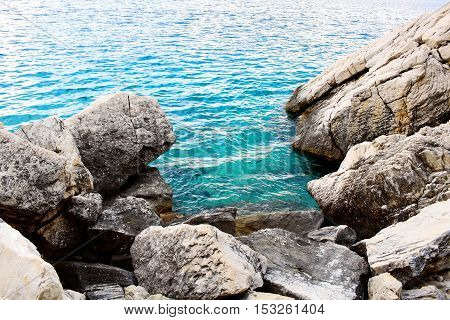 Blue sea or ocean water washes stones or rocks of coast beach seashore on sunny day on seascape background