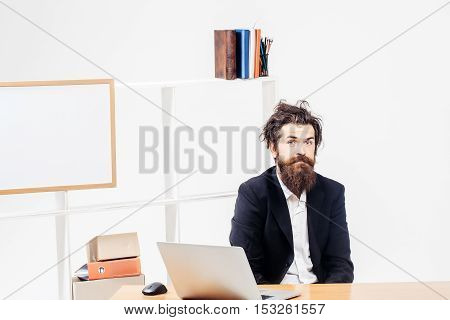 Funny crazy bearded young businessman with tousled hair sitting at office desk at workplace