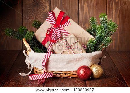 Christmas gift boxes and fir tree branch in basket on wooden table