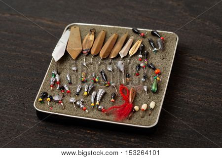 Set of lures for ice fishing on wooden surface