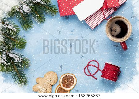 Christmas background with gift boxes, coffee and fir tree on stone table. Top view with copy space. Gift wrapping