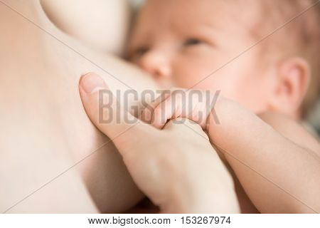 Close-up portrait of sweet newborn baby breastfeeding. Adorable new born caucaian kid holding moms finger with his cute little palm while breast feeding. Focus on hands. Young mother nursing baby