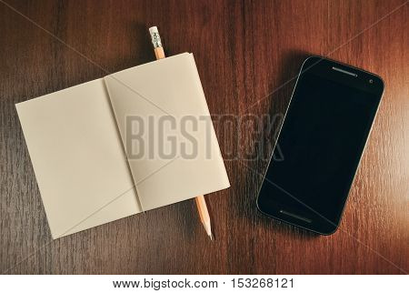 Open pocket book pencil and mobile smart phone on wooden table mock up top view