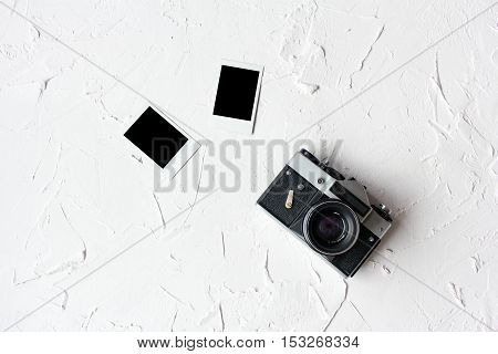 Stack of photos and old camera on white table