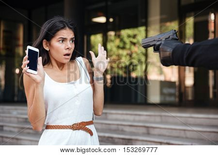 Scared young woman with blacnk screen cell phone threatened by criminal with gun on the street