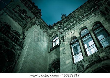 Spooky dark castle house hallowen with bright vintage window