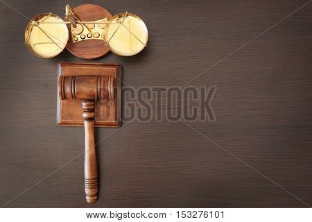 Justice scales and judge's gavel on wooden table, top view