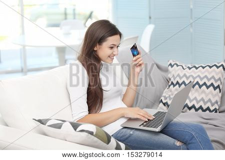 Young happy woman with laptop and credit card making online shopping