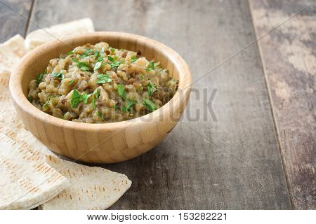Eggplant baba ganoush and pita bread on wooden table