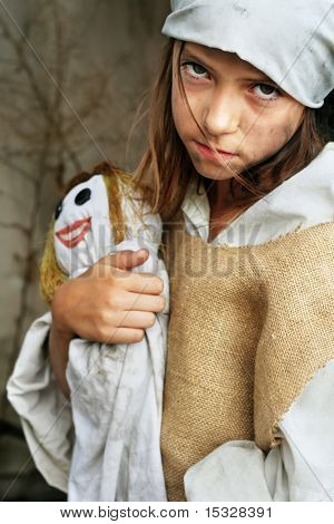 Sad child wearing vintage, dirty clothing,  holding a smiling doll. More available. poster
