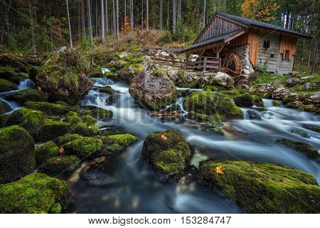 Old Water Mill. Image of the old wooden water mill in the middle of the forest with the mountain creek in the foreground.