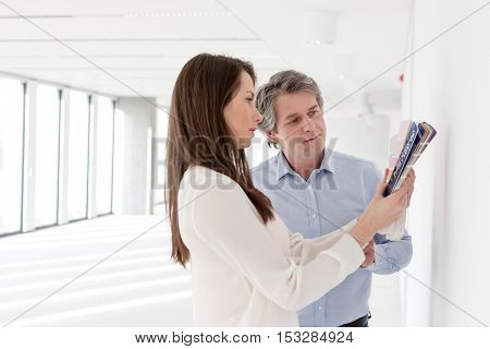 Business people choosing color samples against wall in empty office