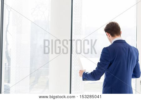 Rear view of young businessman reading blueprint in new office