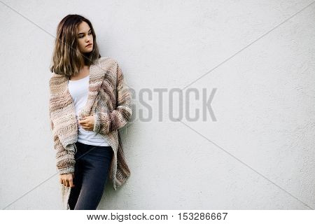 Woman In Woolen Sweater Posing Against A White Wall