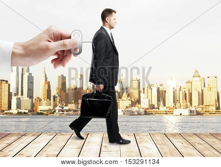 Hand turning winder on business person's back. City view background. Control concept
