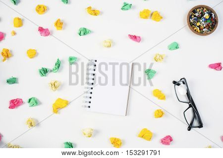 Top view of messy office desktop with blank spiral notepad glasses colorful supplies and crumpled paper balls. Mock up