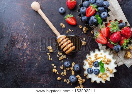 Breakfast, healthy food concept. Homemade muesli granola and yogurt with berries honey in a rustic bowl on rusty black table. Selective focus, copy space background, top view overhead flat lay