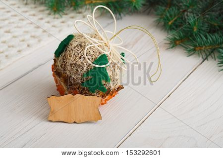 Creative diy craft hobby. Craft handmade christmas ball with felt spruce tree and empty wooden lable with copy space. Home leisure, holiday decorations. Closeup of female hands at wood background