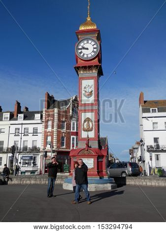 Weymouth England - October 10 2016: People enjoying autumn sunshine at the Queen Victoria Jubilee Memorial
