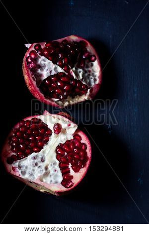 pomegranate fruit on a black background in darkness light