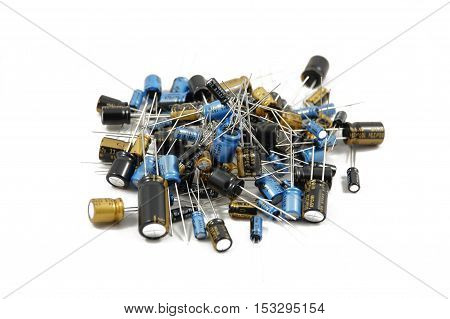 Lots of different capacitors isolated on white background, piled up together