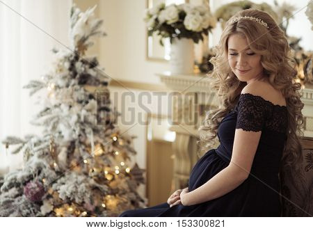 Beautiful Pregnant Woman In A Holiday Dress. Christmas Tree Background.