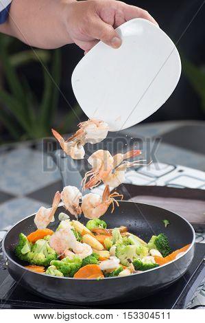 Chef putting shrimp to pan / cooking stir fry Broccoli concept