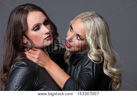 Fight blonde with brunette. Two girl friends quarrel.
