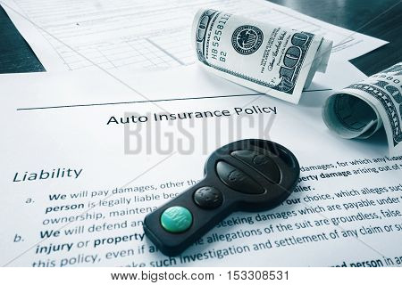 Car insurance policy with money and key fob