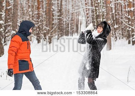 Snowball fight. Winter couple having fun playing in snow outdoors