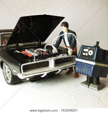 Vintage Star Wars figures Han Solo jump starts a 1969 Dodge Charger with a GONK power droid