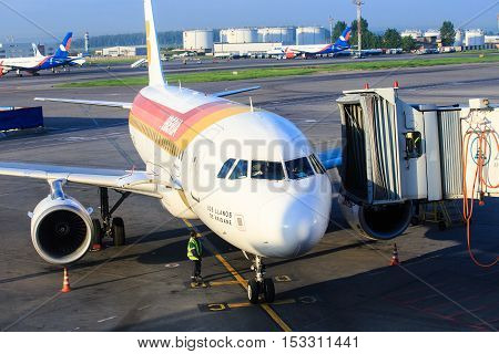 Moscow, Russia - May 27, 2016:  Iberia airlines aircraft prepares for boarding passengers through a telescopic ladder at the Domodedovo airport in Moscow, early morning