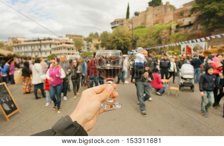 Many people with families walking down the celebration streets with wine during autumn city festival Tbilisoba. Tbilisi, the capital of Georgia country