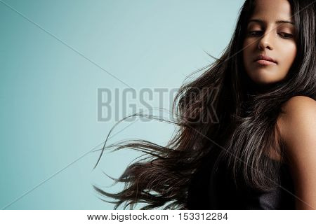 Woman With Blowed Brunette Hair On Blue