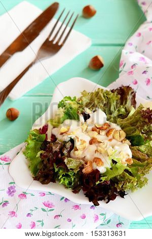 Mix of salad leaves with yogurt and nuts on a plate. Salad is prepared from radicchio, lettuce, iceberg, frieze. Healthy food. Fork, knife, napkin, raw hazelnuts on a wooden background. Closeup