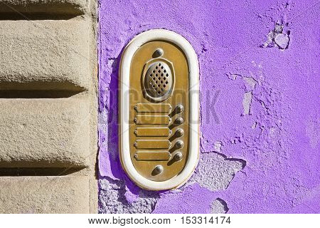Old colored bell system on purple plaster (Tuscany - Italy)