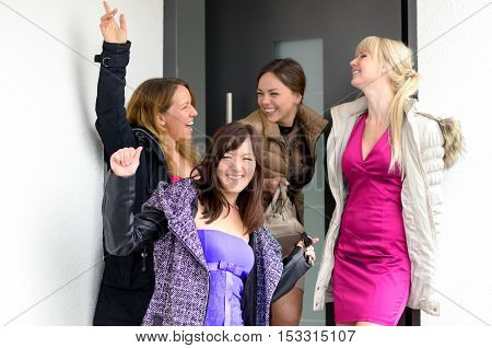 Happy laughing group of stylish young women in evening wear posing in an open doorway waving and grinning at the camera