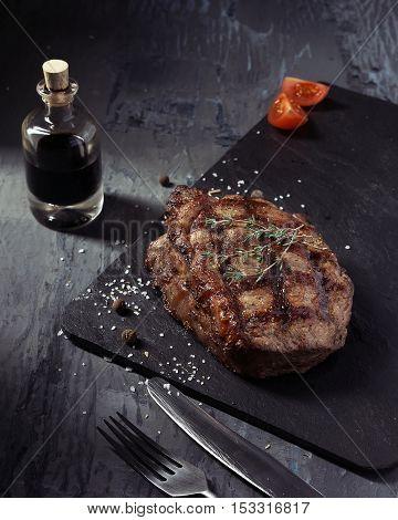 Closeup of medium rare roast beef steak with herbs and bottle of sauce