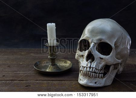 Human skull with candle on wood floor