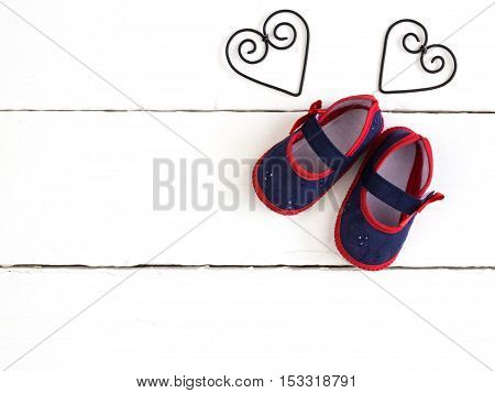 Overhead photo of pair of navy and red baby booties heart metal frame shapes isolated on white wood table