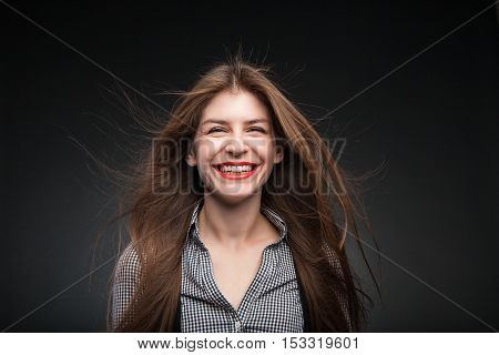 Portrait of adorable girl grins with red lipstick on her lips. Studio portrait on black vignette background.