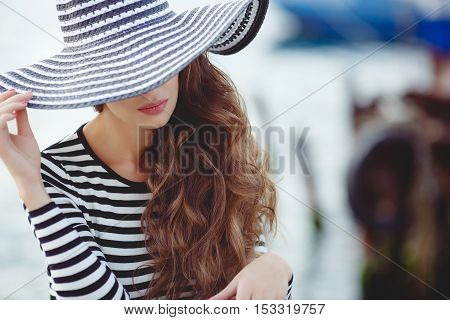 Beautiful young woman model looks,brunette with long curly hair,on his head wearing striped straw hat with a large brim pulled down to his eyes,dressed in a striped summer dress,spends time on the ocean, close to Parking of boats and yachts