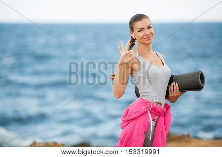 A young woman,athletic,brunette with long hair braided in a braid,in a gray shirt and gray sweat pants,a belt tied a pink sports jacket,ready to perform fitness exercises on the beach in the fresh air on a dark gray mat that holds the left-hand