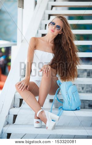 Young beautiful brunette woman with brown long hair, sun glasses, pink lipstick, attractive birthmark near his lower lip, a blue backpack, dressed in a short white suit, posing outdoors in the summer on a white platform near the white wooden steps